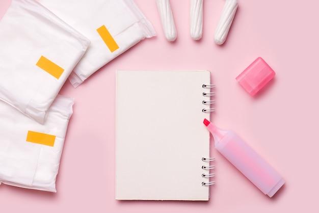 Menstruatiecyclus. notitieboekje is leeg en een stift naast maandverband en tampons