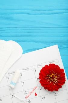 Menstruatiekalender met katoenen tampons en pads op blauwe achtergrond. kritieke dagen van de vrouw, bescherming van de hygiëne van de vrouw. menstruatie pijn