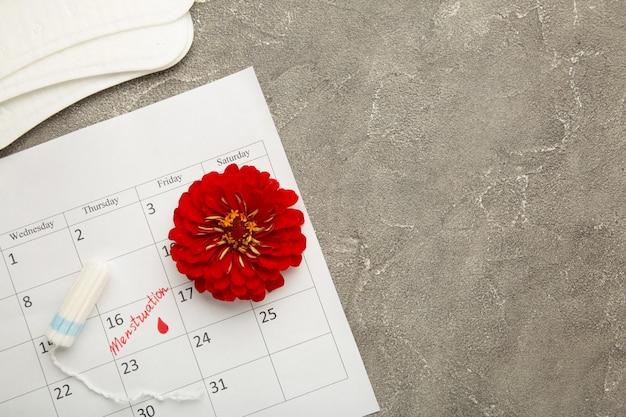 Menstruatiekalender met katoenen tampons en pads op grijze achtergrond. kritieke dagen van de vrouw, bescherming van de hygiëne van de vrouw. menstruatie pijn