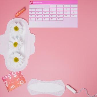 Menstruatiekalender met katoenen tampons, maandverband, witte bloem. kritieke dagen van de vrouw, bescherming van de hygiëne van de vrouw.