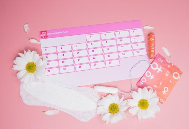 Menstruatiekalender met katoenen tampons, maandverband, witte bloem. kritieke dagen voor vrouwen, bescherming van vrouwenhygiëne.