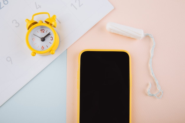 Menstruele cyclus concept. gele wekker en een mobiele applicatie op het smartphonescherm. katoenen tampon op de achtergrond.