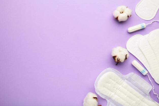 Menstruele tampons en maandverband met katoen op een paarse achtergrond. menstruatie cyclus. hygiëne en bescherming. bovenaanzicht.
