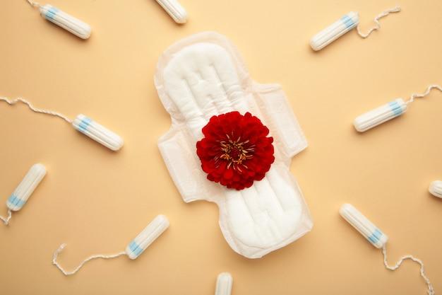 Menstruele tampons en pads op beige achtergrond. een roze bloem ligt op een menstruatiepad. menstruatie cyclus. hygiëne en bescherming. bovenaanzicht. verticale foto