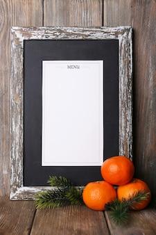Menu bord met kerstversiering en sinaasappelen op houten planken achtergrond