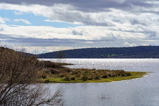 Merenlandschap met planten en bomen in het water, donkere wolken en reflecties van de zon in het water. madrid guadalix. europa.
