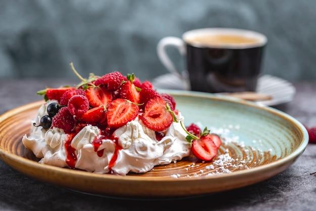 Meringue cake versierd met aardbeien framboos zwarte bes en siroop
