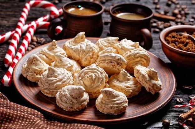 Meringue-koekjes geserveerd op een bord met kerstsuikerriet, koffiekopjes, koffiebonen, bruine suiker en kaneelstokjes op een donkere houten ondergrond, bovenaanzicht, close-up