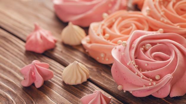 Meringue lichtroze in de vorm van een roos of bloem. meringue is veel taartdecoratie, close-up.