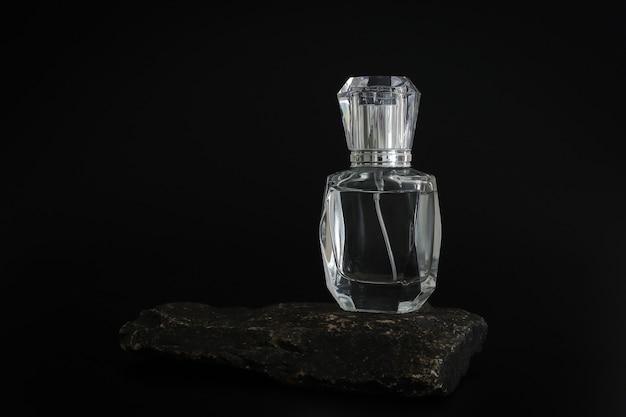 Merkloze parfumfles staande op stenen podium. parfumpresentatie op de zwarte achtergrond. mock-up. trending concept in natuurlijke materialen. de essentie van vrouwen en mannen. natuurlijke cosmetica.
