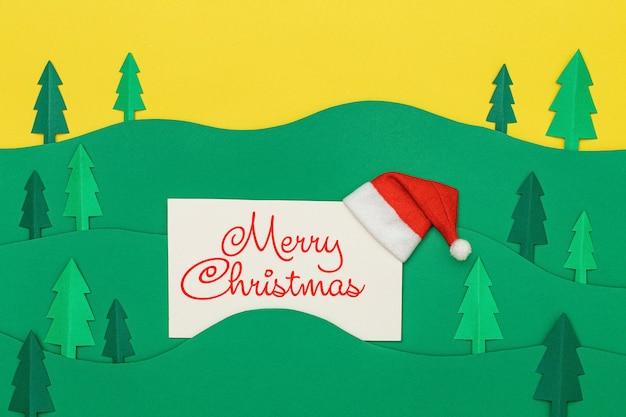 Merry christmas belettering op wenskaart met bomen boslandschap in papier knippen stijl.
