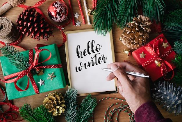 Merry christmas-concepten met menselijke hand die wenskaarten met giftdoos schrijven