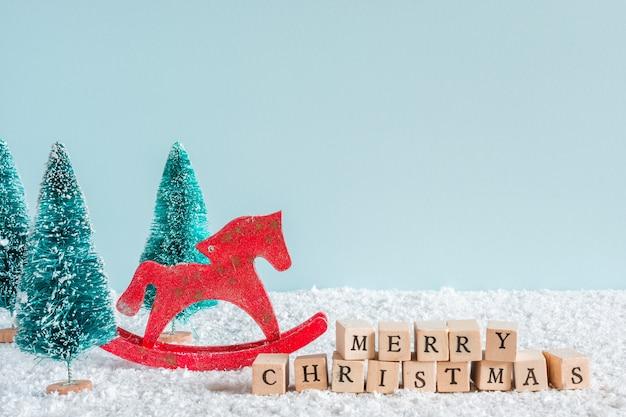 Merry christmas inscriptie met sparren en paard speelgoed op sneeuw achtergrond