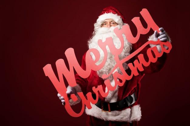 Merry christmas-teken houden door de kerstman