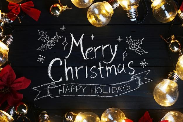 Merry christmas typografie gloeilampen en rode poinsettia op zwart hout.
