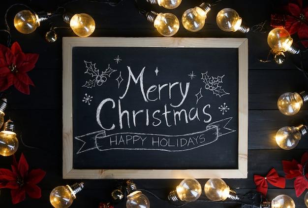 Merry christmas-typografie op bord tussen gloeilampen en rode poinsettia op zwart hout