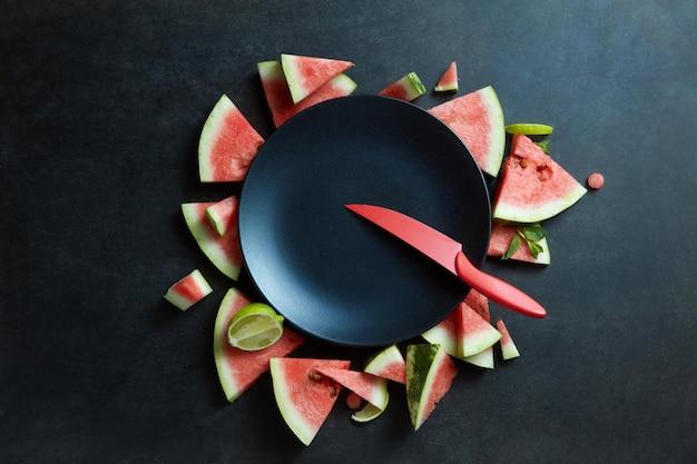 Mes en plakjes watermeloen in een cirkel van zwarte plaat