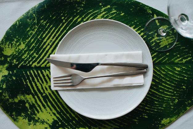 Mes en vork op een servet op een witte plaat. geplaatst op een laken voor een bruiloft