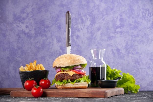 Mes in smakelijke vleessandwichsaus ketchup frietjes op houten snijplank en tomaten met stengel op geïsoleerd ijsoppervlak