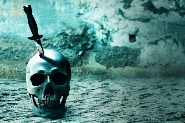 Mes met bloed geplakt op het menselijke schedel halloween-concept