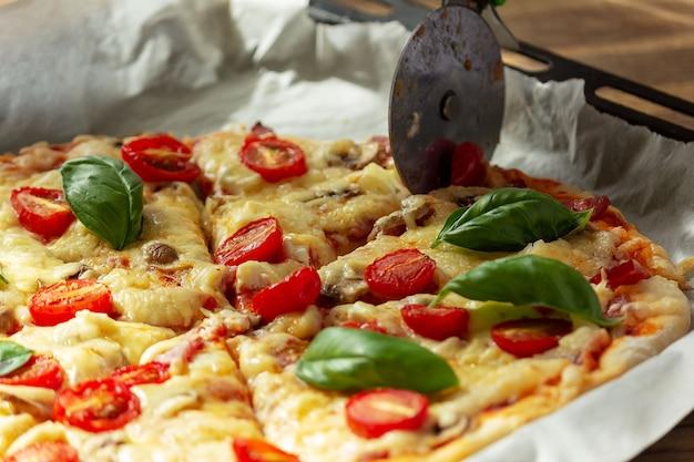 Mes snijdt verse zelfgemaakte pizza op een bakplaat