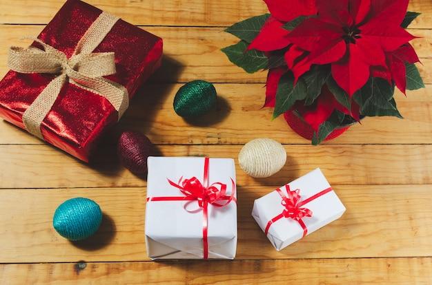 Mesa con cajas de regalos de navidad y maceta con flor de pascuas
