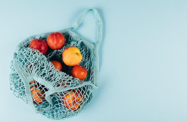 Mesh boodschappentas met fruit plims en perzik op blauw. bovenaanzicht, plat lag, kopie ruimte