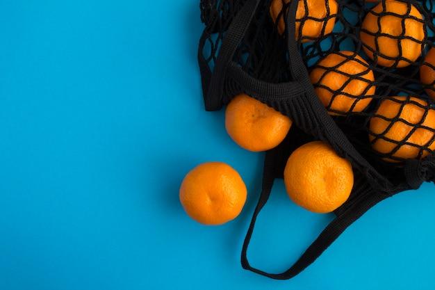 Mesh boodschappentas met mandarijnen op blauw