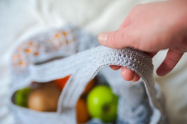Mesh boodschappentas met sinaasappels en appels op verfrommeld textiel.