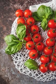 Mesh boodschappentas met tomaten en basilicum. plastic vrij, hergebruik concept. plat lag, bovenaanzicht.