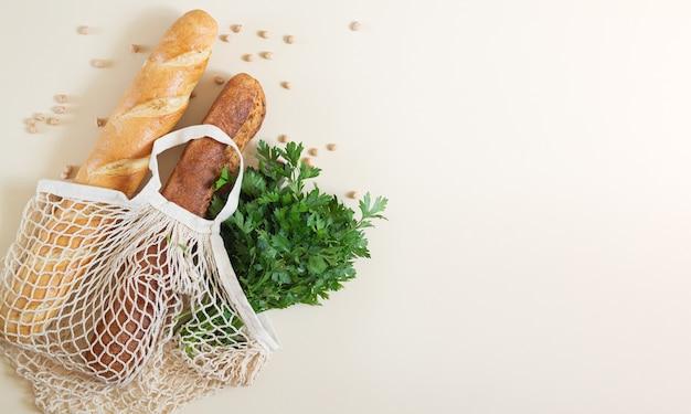 Mesh boodschappentas met vers gebakken stokbrood en peterselie bovenaanzicht met kopie ruimte
