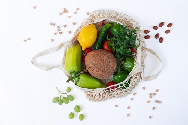 Mesh boodschappentas vol met gezonde voeding op witte achtergrond