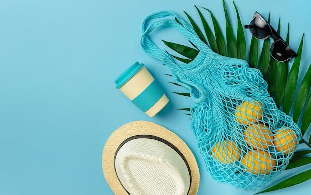 Mesh tas met citroenen, bamboe beker en zomeraccessoires op blauwe achtergrond. ruimte kopiëren, plat leggen