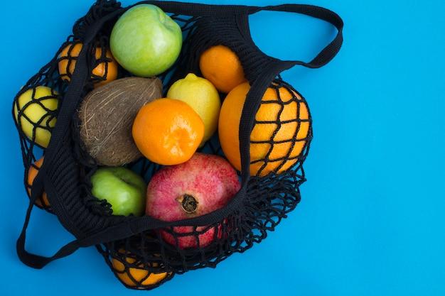 Mesh winkelen zwarte tas met verschillende vruchten op blauw. bovenaanzicht. kopieer ruimte.