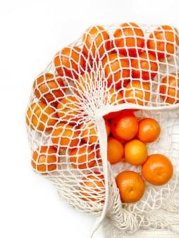 Mesh zakje verse sinaasappelen gezonde citrusvruchten van op wit