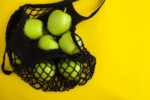 Mesh zwarte boodschappentas met groene appels op het gele oppervlak