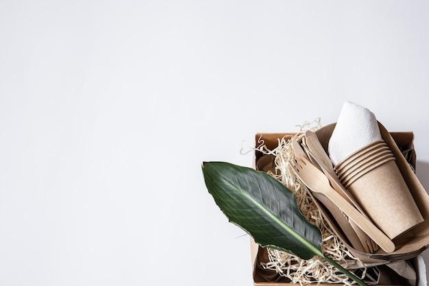 Messen, vorken, bekers, papieren bakjes voor voedsel en een natuurlijk blad. het concept van nul afval en plasticvrij.