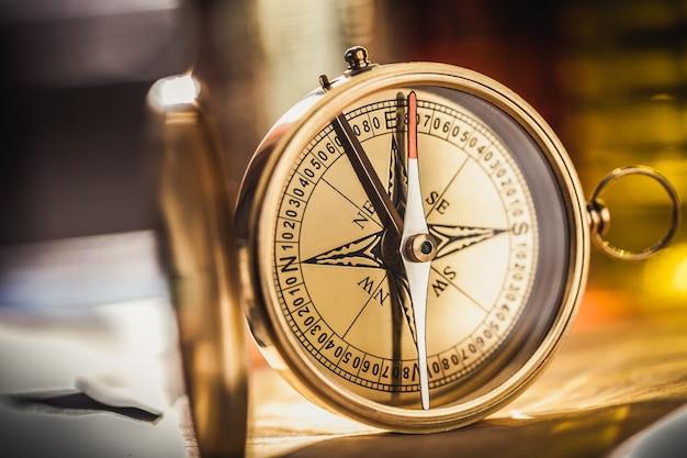 Messing antiek kompas op onscherpe achtergrond