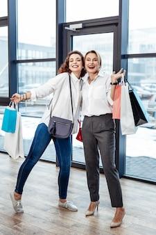 Met aankopen. mooie vrolijke en stijlvolle vrouwen die zich gelukkig voelen terwijl ze de winkel verlaten met aankopen