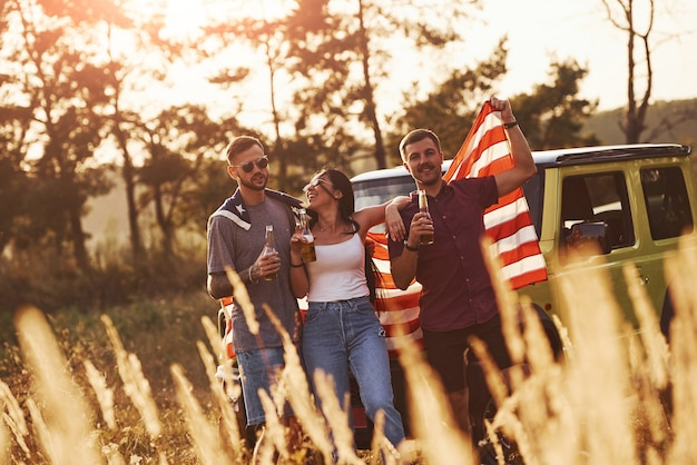 Met alcohol in handen. vrienden hebben een leuk weekend buiten in de buurt van hun groene auto met vlag van de v.s.