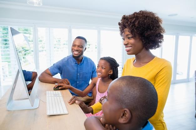 Met behulp van computer in de woonkamer en gelukkige familie