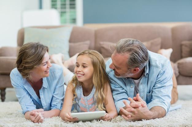 Met behulp van digitale tablet liggend op de vloer in de woonkamer en gelukkige familie