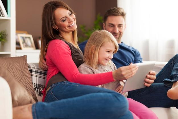 Met behulp van digitale tablet thuis en gelukkige familie
