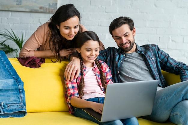 Met behulp van een laptop en gelukkige familie