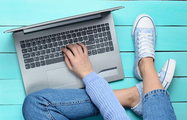 Met behulp van een laptop op een turquoise houten tafel. bovenaanzicht moderne jeugd. generatie z. online werken op internet.