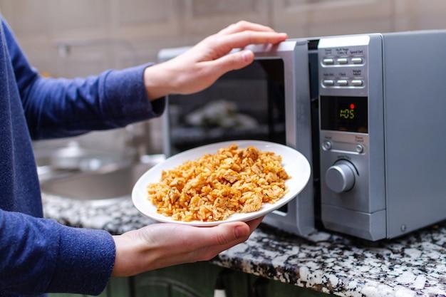 Met behulp van een magnetron om thuis een bord zelfgemaakte pilaf op te warmen. warme maaltijd