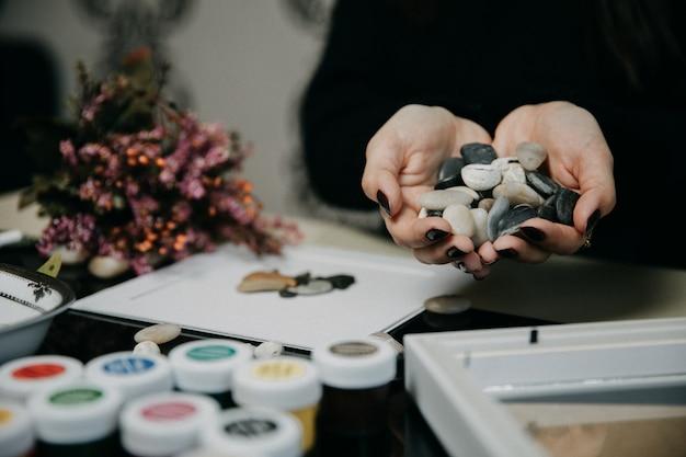 Met behulp van kleine stukjes steen en acryl in het atelier