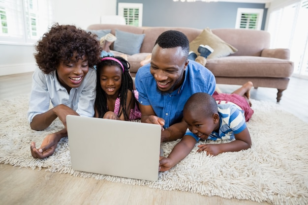 Met behulp van laptop in de woonkamer en gelukkige familie