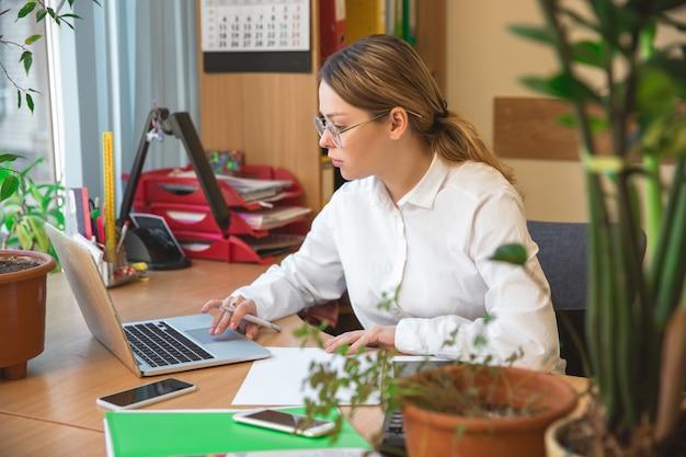 Met behulp van laptop. ondernemer, zakenvrouw, manager werken geconcentreerd in kantoor