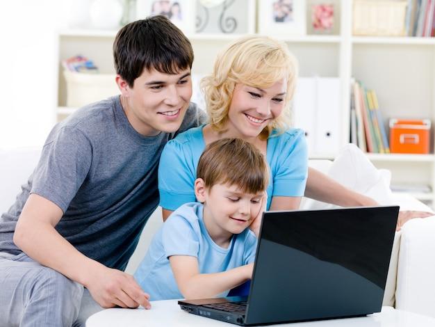 Met behulp van laptop thuis en gelukkige familie